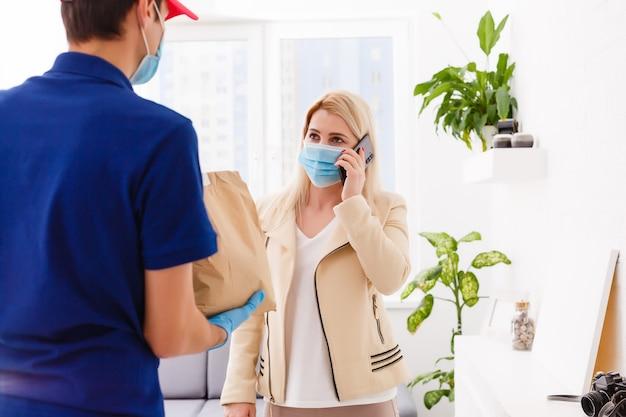 Livreur tenant un sac en papier avec de la nourriture sur fond blanc, livreur de nourriture en masque de protection et gants de protection