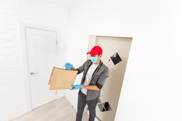 Livreur tenant un sac en papier avec de la nourriture sur fond blanc, livreur de nourriture en masque de protection