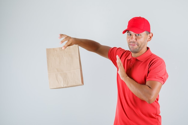 Livreur tenant un sac en papier en uniforme rouge et à la protection