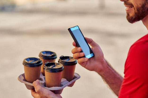 Livreur tenant un smartphone et des tasses à café sur le plateau de livraison à l'extérieur, recadré. concept de livraison de nourriture