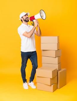 Livreur sur toute la longueur entre des boîtes sur un mur jaune isolé criant à travers un mégaphone