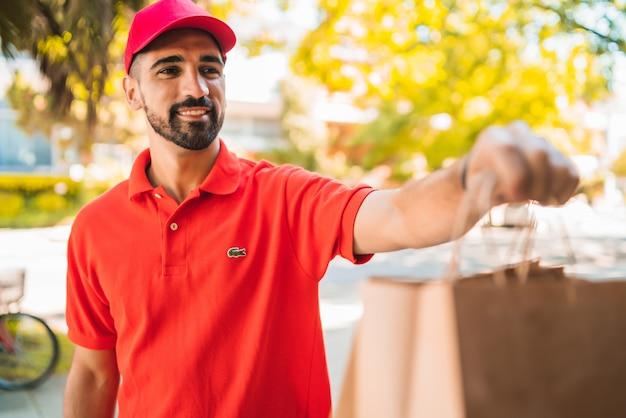 Livreur transportant des colis lors de la livraison à domicile