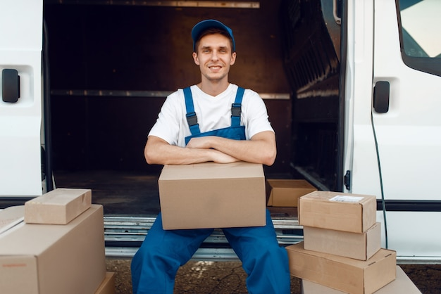 Livreur en uniforme assis entre les colis et les boîtes en carton, service de livraison, prestation de l'occupation. l'homme pose à des emballages en carton dans un véhicule, un homme livre, un service de messagerie ou un travail d'expédition
