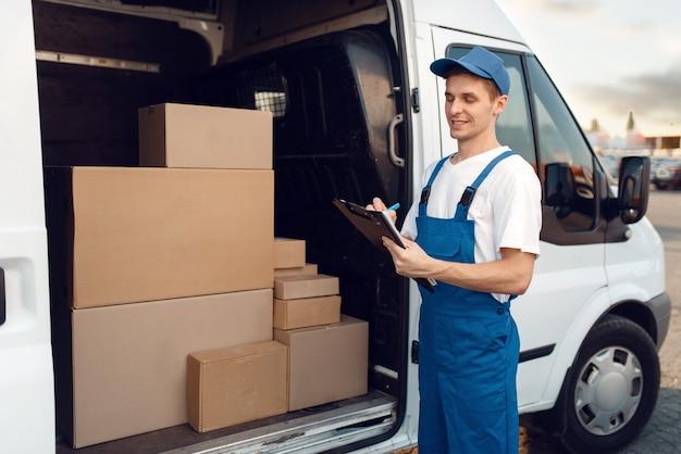 Livreur en uniforme, cartons dans la voiture, service de livraison. homme debout à des colis en carton dans un véhicule, un homme livrer, un courrier ou un travail d'expédition