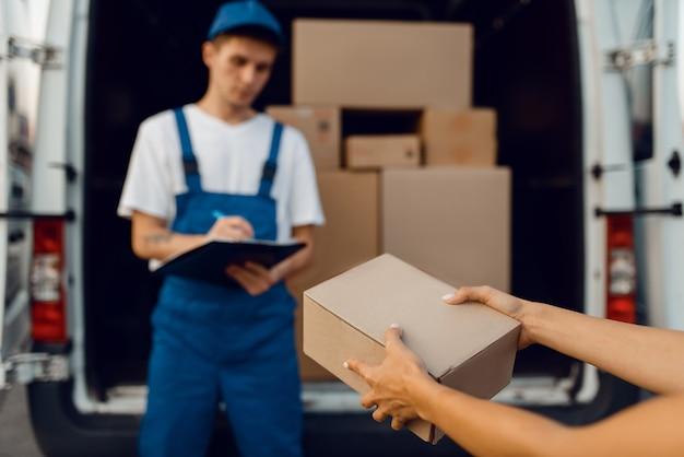 Livreur en uniforme donne le colis à l'acheteur féminin à la voiture, service de livraison, livraison. homme tenant un paquet en carton près du véhicule, homme livrer et femme, courrier ou travail d'expédition