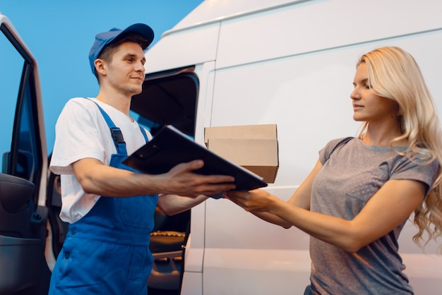 Livreur en uniforme donne un colis à une cliente à la voiture, service de livraison. homme tenant un paquet en carton près du véhicule, homme livrer et femme, courrier ou travail d'expédition