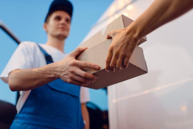 Livreur en uniforme donne un colis à une destinataire à la voiture, service de livraison. homme tenant un paquet en carton près du véhicule, homme livrer et femme, courrier ou travail d'expédition