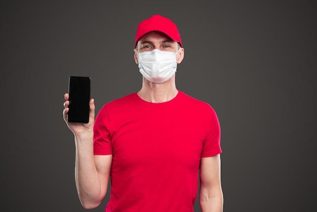 Livreur en uniforme et masque montrant l'application sur smartphone avec écran noir tout en faisant la publicité d'un service logistique pendant l'épidémie de coronavirus sur fond gris