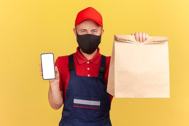 Livreur en uniforme et masque de protection sur le visage tenant et montrant un sac en papier et un smartphone