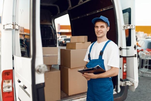 Livreur en uniforme pose à la voiture avec des boîtes à colis, service de livraison. homme debout à des colis en carton dans un véhicule, un homme livrer, un courrier ou un travail d'expédition