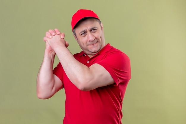 Livreur en uniforme rouge et cap debout avec un geste de travail d'équipe souriant confiant sur espace vert isolé