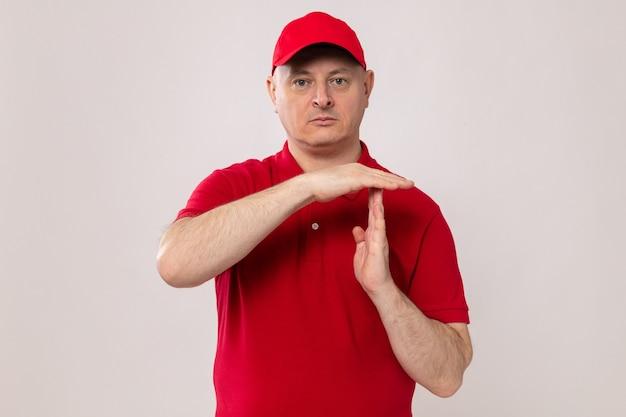 Livreur en uniforme rouge et casquette regardant avec un visage sérieux faisant un geste de temps mort avec les mains