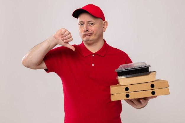 Livreur en uniforme rouge et casquette tenant des boîtes à pizza et des emballages alimentaires à l'air mécontent montrant les pouces vers le bas
