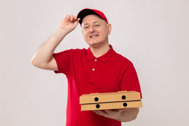 Livreur en uniforme rouge et casquette tenant des boîtes à pizza regardant la caméra heureux et positif souriant confiant debout sur fond blanc