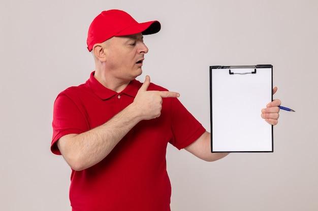 Livreur en uniforme rouge et casquette tenant le presse-papiers avec des pages blanches pointant avec l'index sur eux avec un visage sérieux debout sur fond blanc
