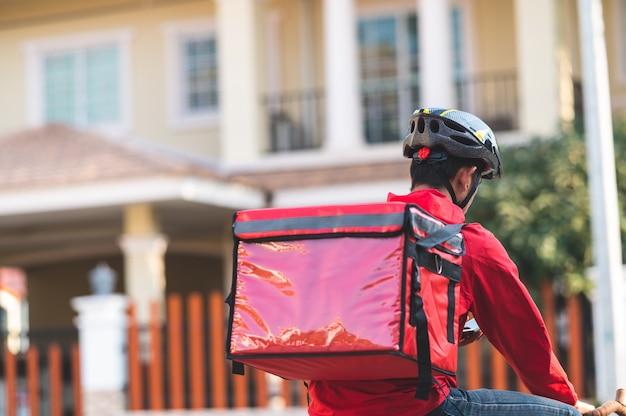 Livreur en uniforme rouge à vélo pour livrer les produits aux clients à la maison.