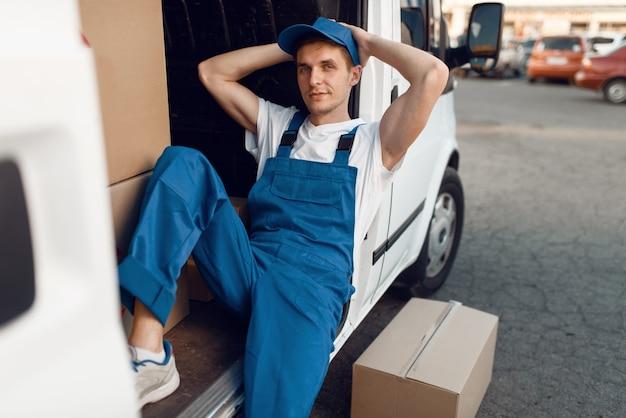 Livreur en uniforme se détendre dans la voiture pendant une pause, auto avec colis et boîtes en carton, service de livraison. l'homme pose à des emballages en carton dans un véhicule, un homme livre, un service de messagerie ou un travail d'expédition