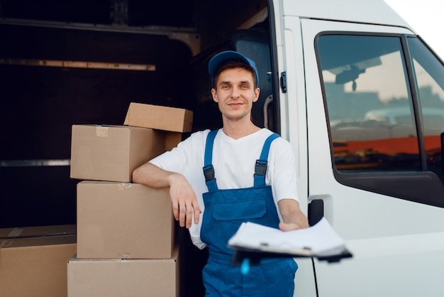 Livreur en uniforme tenant colis et cahier, boîtes en carton dans la voiture, service de livraison. homme, debout, à, emballages carton, dans, véhicule, homme, livrer