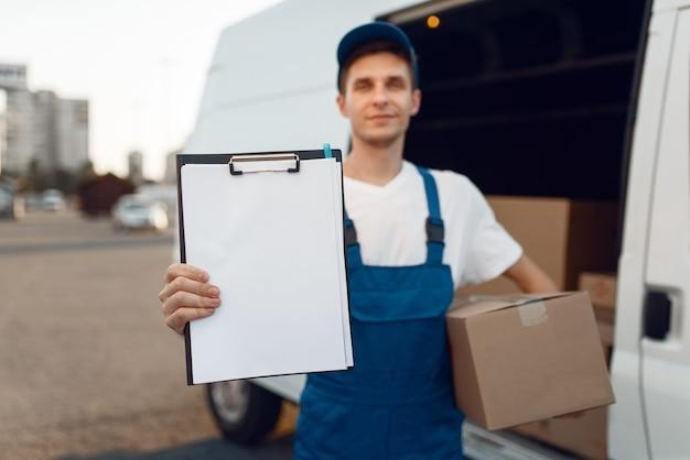 Livreur en uniforme tenant colis et cahier, boîtes en carton dans la voiture, service de livraison.