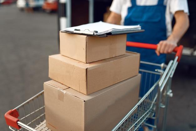 Livreur en uniforme tient le chariot avec pile de boîtes à la voiture avec des colis, service de livraison. homme debout à des colis en carton dans un véhicule, un homme livrer, un courrier ou un travail d'expédition