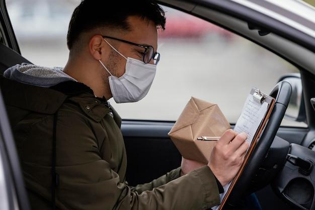 Livreur de vue latérale avec masque en voiture