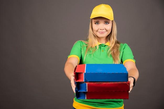 Livreuse en uniforme donnant des cartons de pizza.