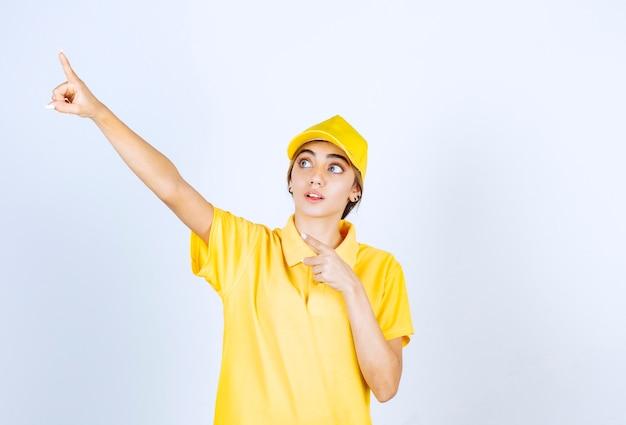 Livreuse en uniforme jaune debout et pointant vers le haut.