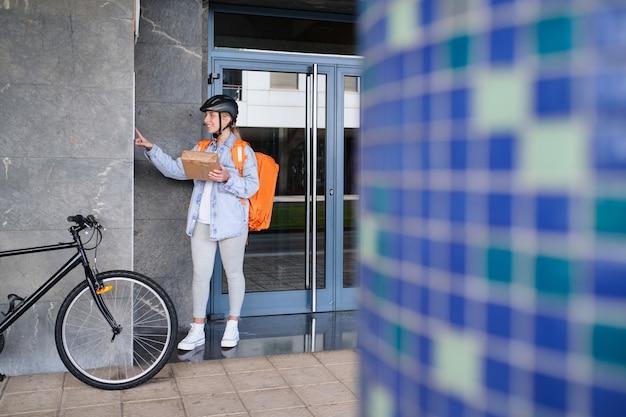 Une livreuse à vélo sonne à la porte d'une maison pour effectuer une livraison