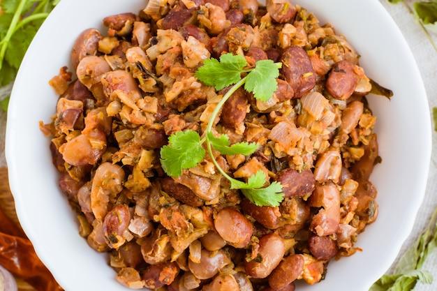 Lobio - le plat national géorgien de haricots dans une assiette blanche et les ingrédients pour sa préparation sur une table en bois