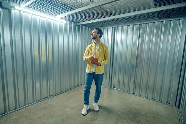 Location, conteneur. heureux homme en chemise jaune et jeans avec tablette debout à l'intérieur d'un garage en fer vide regardant autour avec intérêt