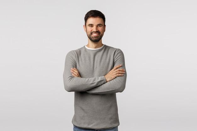 Location, emploi et concept d'entreprise. enthousiaste beau homme barbu caucasien en pull gris, bras croisés poitrine, souriant heureux et sûr de lui, h interviewer l'employé