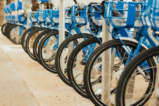 Location de vélos bleus aux stations d'accueil en ville le long d'une rue animée