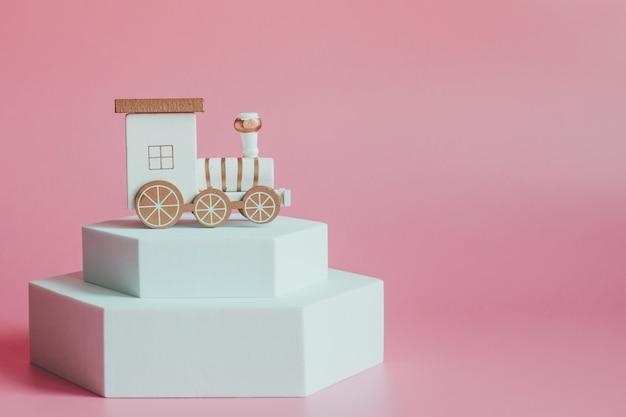 Locomotive jouet de noël sur une plate-forme blanche, sur rose