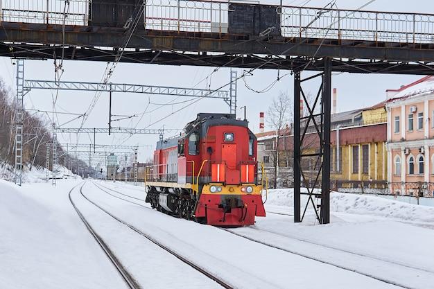 Locomotive de manœuvre sur une voie ferrée dans une zone industrielle un jour d'hiver nuageux