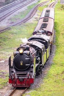 Locomotive à vapeur approchant d'une gare.