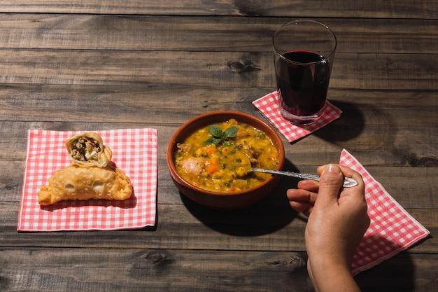 Locro et empanadas de cuisine argentine typique sur un fond en bois.