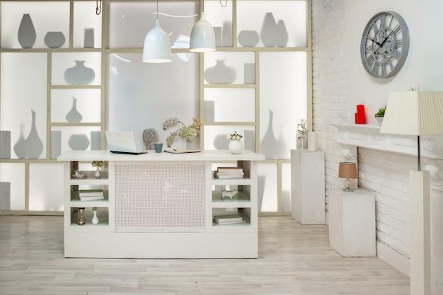 Loft blanc moderne. avec un support lumineux au milieu, avec une lumière spéciale sur le mur arrière.