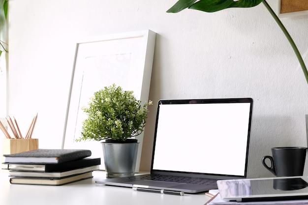 Loft de lieu de travail à la maison avec ordinateur portable, affiche et fournitures.
