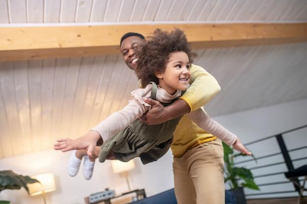 Loisirs actifs. papa afro-américain debout soutenant une petite fille joyeuse dans l'air jouant à l'avion à la maison dans une pièce lumineuse