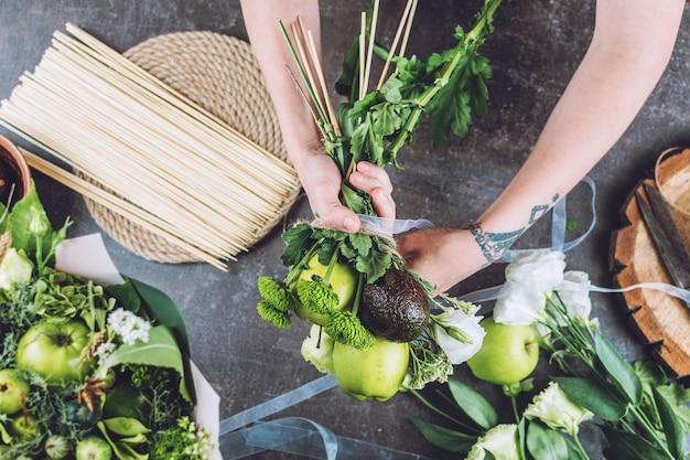 Loisirs et activités arts et artisanat pendant que la fleuriste du coronavirus fabrique un bouquet de fruits comestibles