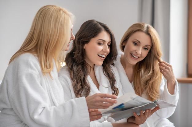 Loisirs. adultes souriantes belles femmes aux cheveux longs en blouse blanche regardant le magazine passer du temps libre ensemble dans une pièce lumineuse