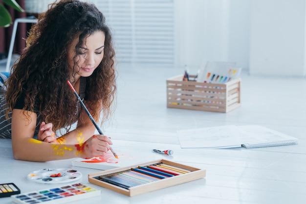 Loisirs artistiques. femme créant une peinture abstraite. crayons de couleur, palette sur parquet blanc.