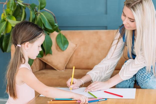 Loisirs artistiques pour enfants. passe-temps d'art de peinture. petite fille et sa maman dessinant des images avec des crayons.