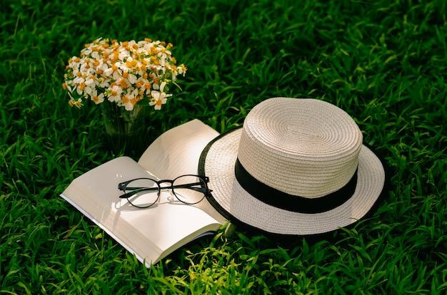 Loisirs dans le jardin avec livre, chapeau de paille et fleurs sur la pelouse.