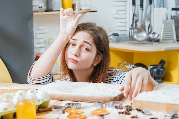 Loisirs à domicile. portrait de femme fatiguée assis dans la cuisine, les mains couvertes de farine, en attente de biscuits prêts.