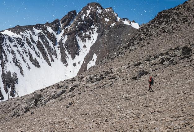 Loisirs extrêmes et tourisme de montagne. un touriste masculin descend un sentier de montagne lâche. en arrière-plan, de grandes montagnes enneigées. vue panoramique.