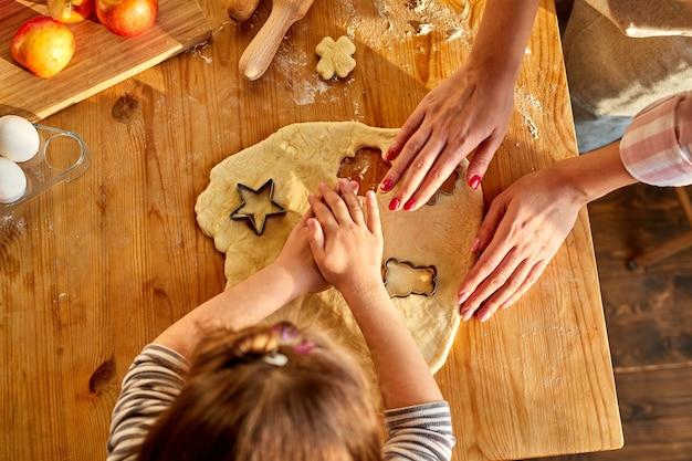 Loisirs en famille en cuisine. mère sympathique enseignant à sa fille comment faire des biscuits à partir de pâte