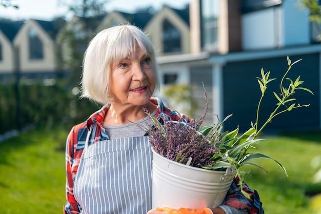 Loisirs. jolie femme de bonne humeur tenant une plante tout en travaillant dans le jardin