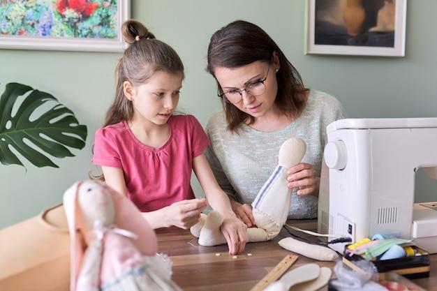 Loisirs et loisirs créatifs à la main en famille, mère et fille de l'enfant cousent ensemble une poupée de lapin. la femme enseigne des techniques de couture de fille, parlant