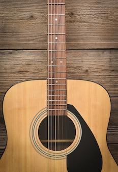 Loisirs à la maison, guitare reposant sur le vieux fond en bois, gros plan de la guitare acoustique